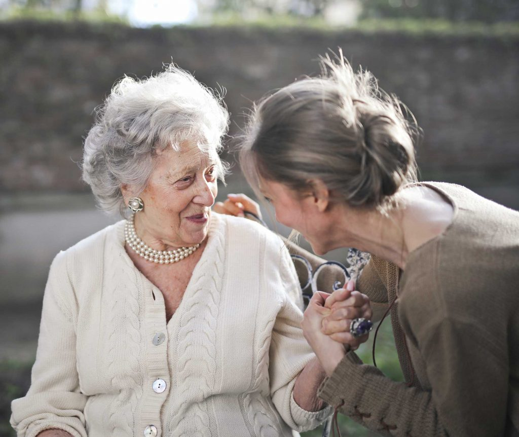 An older woman is comforted and cared for by a younger woman