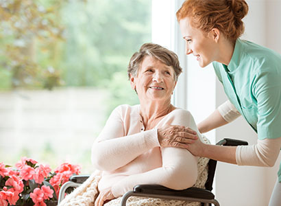 A female nurse cares for an older woman in a wheelchair. They are both smiling.
