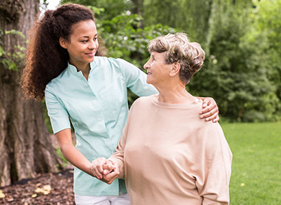 A female nurse assists a patient walking outdoors.