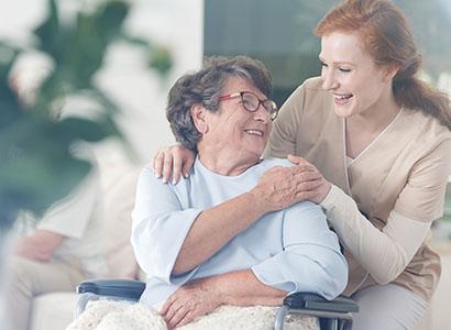 A female nurse assists an older woman in a wheelchair