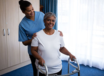 A female nurse assists a patient trying to use a walker.